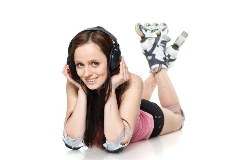 La mujer joven hermosa en rollerskates imagen de archivo