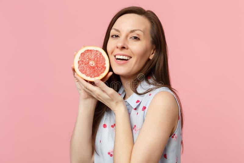 La mujer joven hermosa en ropa del verano lleva a cabo mitad disponible del pomelo maduro fresco aislado en la pared en colores p fotografía de archivo
