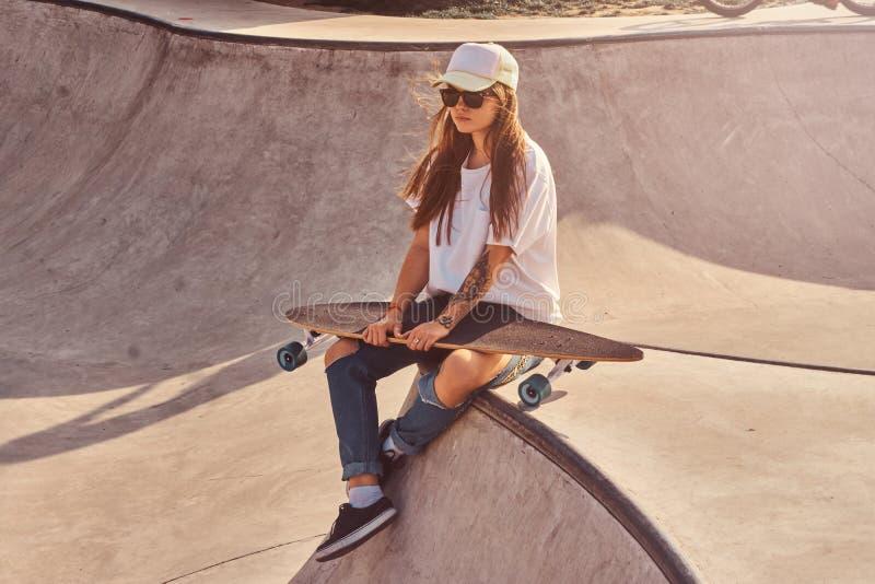 La mujer joven hermosa en sunglacces y casquillo se est? sentando en el skatepark fotos de archivo libres de regalías