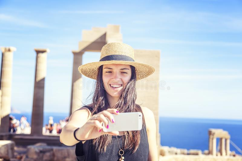 La mujer joven hermosa en un sombrero hace el selfie en el fondo de foto de archivo