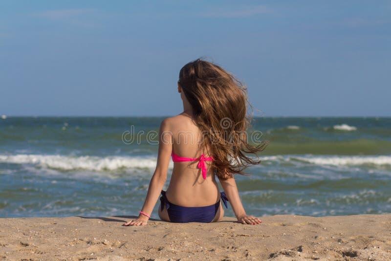 La mujer joven hermosa en un traje de baño con el pelo largo se sienta en la playa cerca del mar imagen de archivo