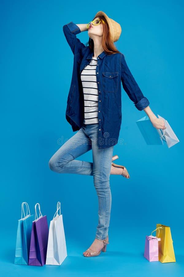 La mujer joven hermosa en vidrios y en un sombrero lleva a cabo muchos paquetes en un hinojo azul, integral, el hacer compras, sh foto de archivo libre de regalías
