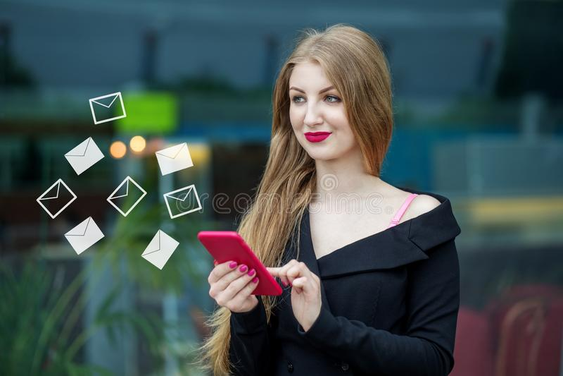 La mujer joven hermosa escribe mensajes en línea El concepto de Internet, tecnología, redes sociales, comunicación y imagen de archivo