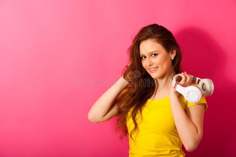 La mujer joven hermosa escucha la música sobre el CCB vibrante del color imágenes de archivo libres de regalías