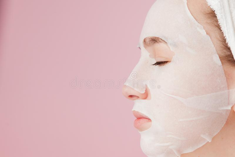 La mujer joven hermosa está aplicando una máscara cosmética del tejido en una cara en un fondo rosado Tratamiento de la atención  fotos de archivo
