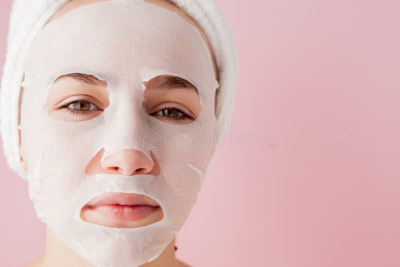 La mujer joven hermosa está aplicando una máscara cosmética del tejido en una cara en un fondo rosado Tratamiento de la atención  imagen de archivo libre de regalías