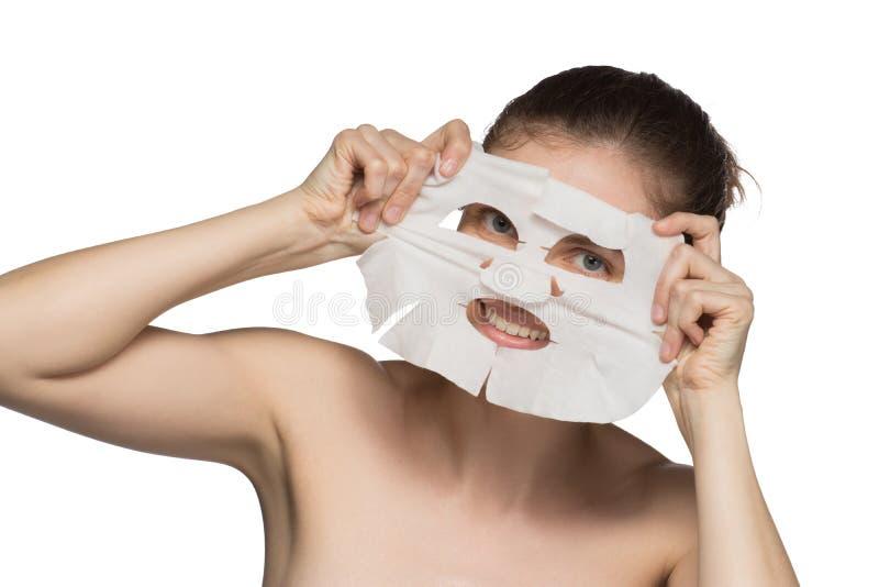 La mujer joven hermosa está aplicando una máscara cosmética y está sonriendo encendido foto de archivo