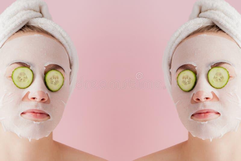 La mujer joven hermosa est? aplicando una m?scara cosm?tica del tejido en una cara con el pepino en un fondo rosado imágenes de archivo libres de regalías