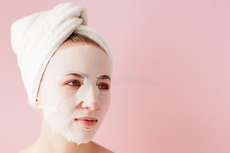 La mujer joven hermosa est? aplicando una m?scara cosm?tica del tejido en una cara en un fondo rosado fotos de archivo libres de regalías