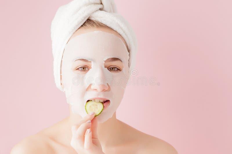 La mujer joven hermosa est? aplicando una m?scara cosm?tica del tejido en una cara en un fondo rosado Tratamiento de la atenci?n  imágenes de archivo libres de regalías