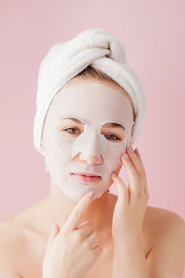 La mujer joven hermosa est? aplicando una m?scara cosm?tica del tejido en una cara en un fondo rosado Tratamiento de la atenci?n  imagen de archivo libre de regalías