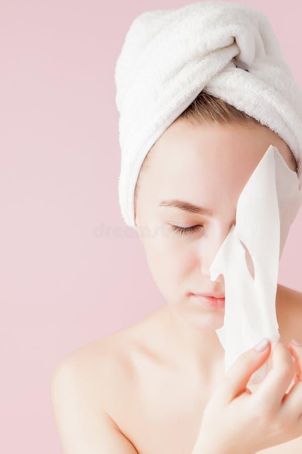 La mujer joven hermosa est? aplicando una m?scara cosm?tica del tejido en una cara en un fondo rosado Tratamiento de la atenci?n  imagenes de archivo