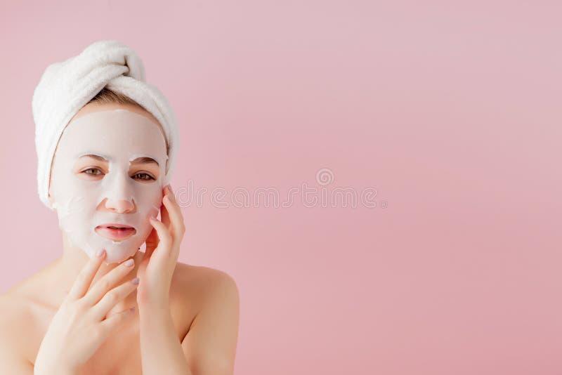 La mujer joven hermosa est? aplicando una m?scara cosm?tica del tejido en una cara en un fondo rosado Tratamiento de la atenci?n  foto de archivo libre de regalías