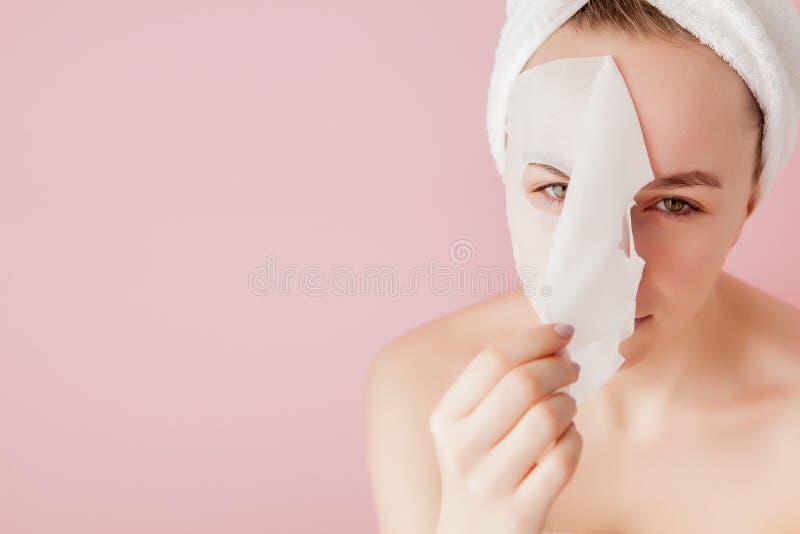 La mujer joven hermosa est? aplicando una m?scara cosm?tica del tejido en una cara en un fondo rosado Tratamiento de la atenci?n  foto de archivo