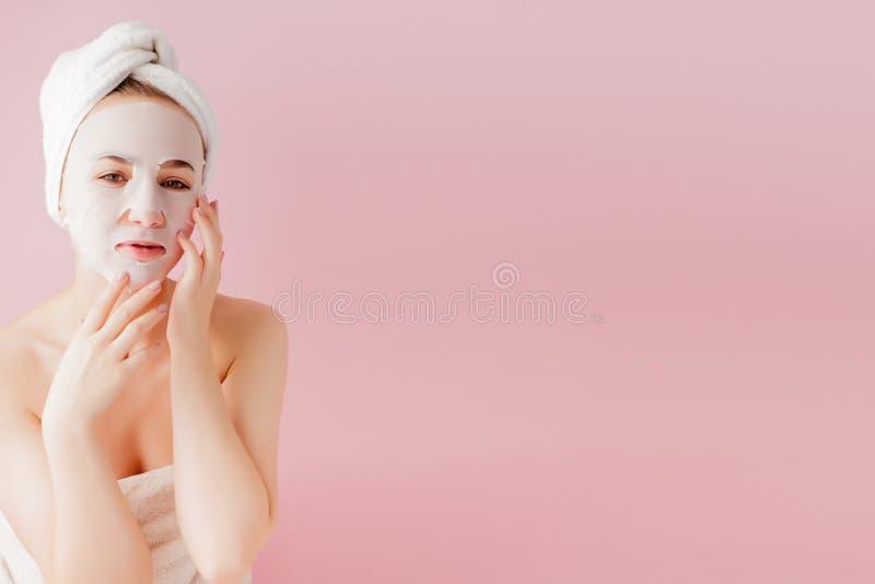 La mujer joven hermosa est? aplicando una m?scara cosm?tica del tejido en una cara en un fondo rosado Tratamiento de la atenci?n  fotos de archivo libres de regalías