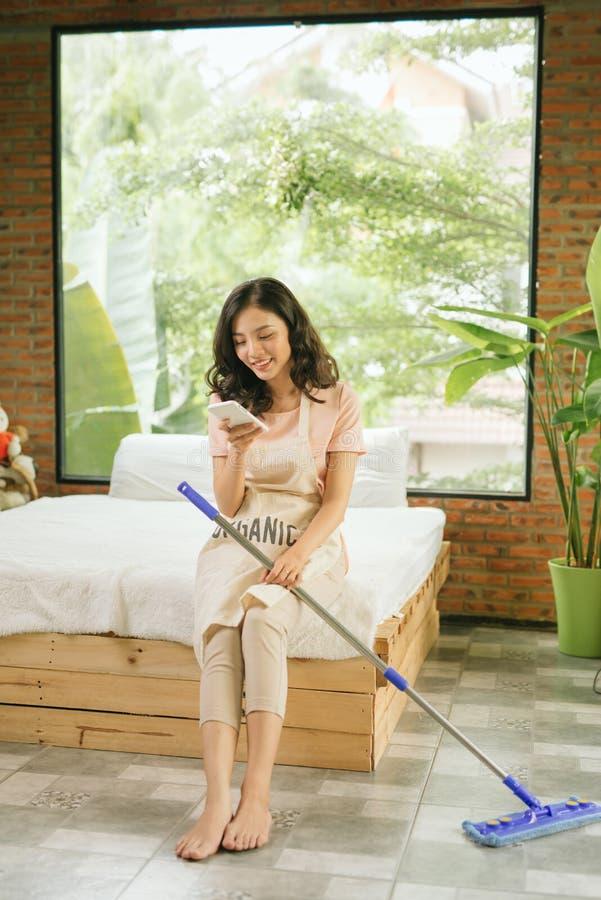 La mujer joven hermosa est? sosteniendo una fregona, usando un smartphone y est? sonriendo mientras que limpia su casa fotografía de archivo libre de regalías