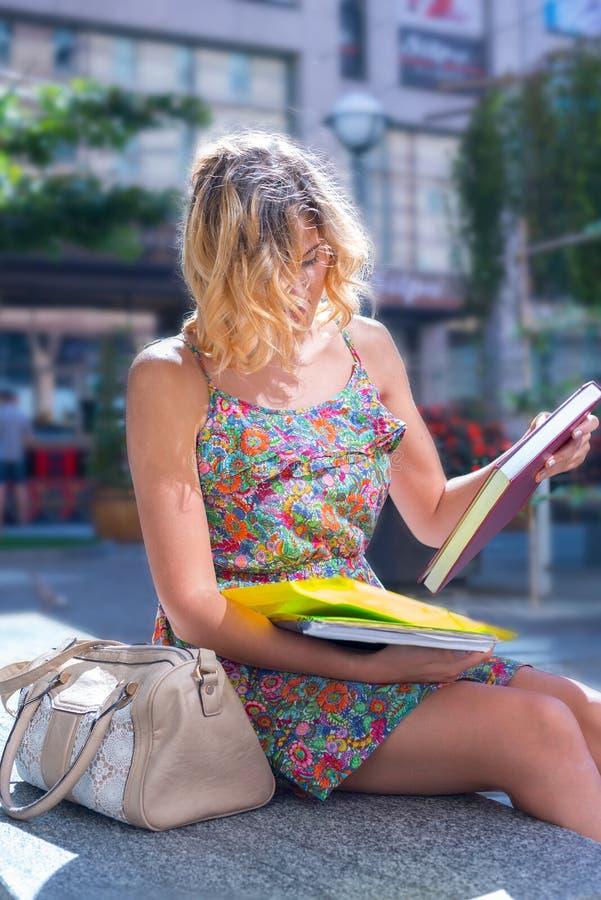 La mujer joven hermosa, estudiante se está sentando en la calle de la ciudad foto de archivo libre de regalías