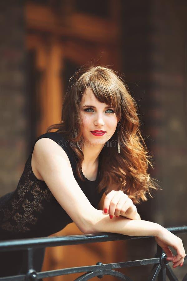 La mujer joven hermosa feliz se inclina en la cerca, la sol foto de archivo libre de regalías