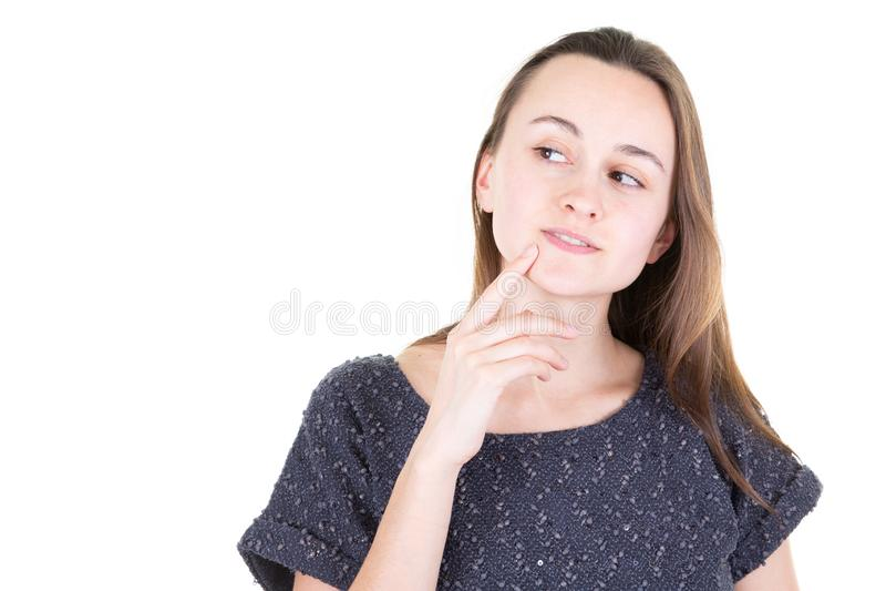 La mujer joven hermosa guarda el finger en cara mira a un lado con actitudes del desconcierto contra el fondo blanco fotografía de archivo