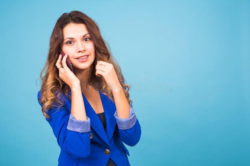La mujer joven hermosa habla hablar por el teléfono móvil en un fondo azul imágenes de archivo libres de regalías