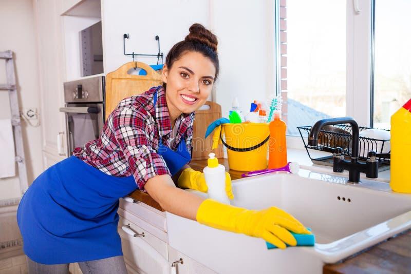 La mujer joven hermosa hace la limpieza de la casa Ki de la limpieza de la muchacha imagen de archivo