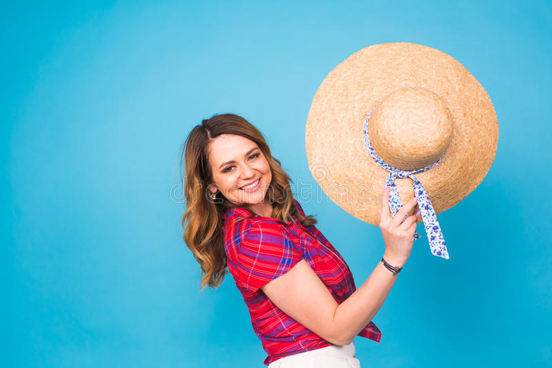 La mujer joven hermosa lleva en vestido del verano y el sombrero de paja está riendo en fondo azul con el espacio de la copia fotografía de archivo libre de regalías
