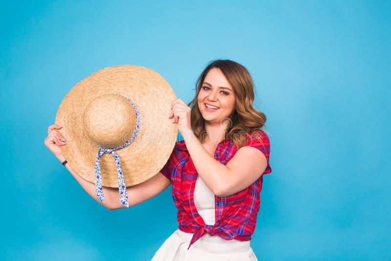 La mujer joven hermosa lleva en vestido del verano y el sombrero de paja está riendo en fondo azul con el espacio de la copia imagenes de archivo