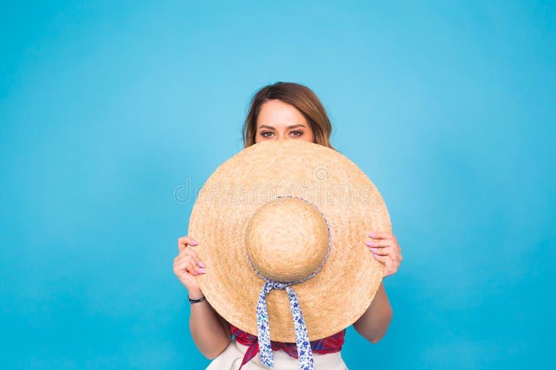 La mujer joven hermosa lleva en vestido del verano y el sombrero de paja está riendo en fondo azul con el espacio de la copia foto de archivo libre de regalías