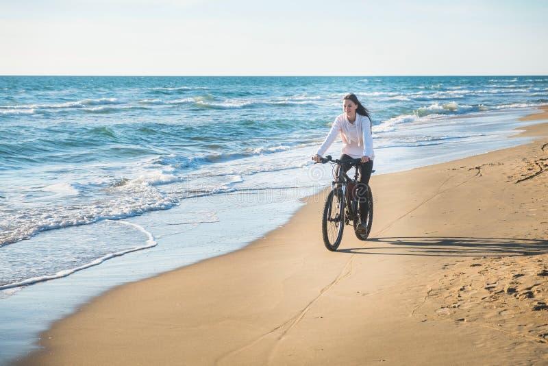 La mujer joven hermosa monta una bicicleta a lo largo del mar en una playa arenosa foto de archivo libre de regalías