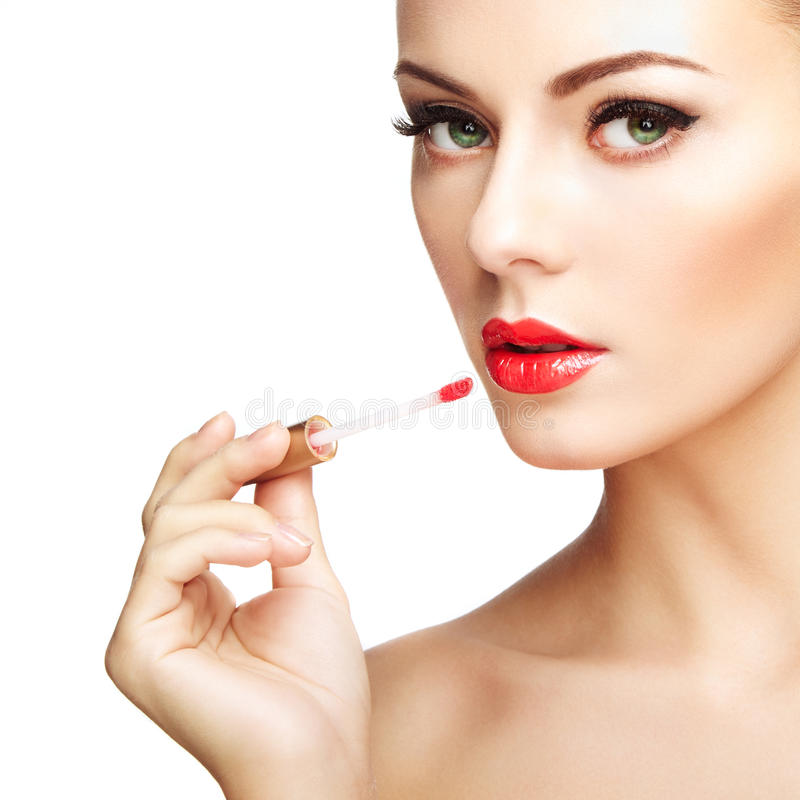La mujer joven hermosa pinta los labios con el lápiz labial fotos de archivo libres de regalías