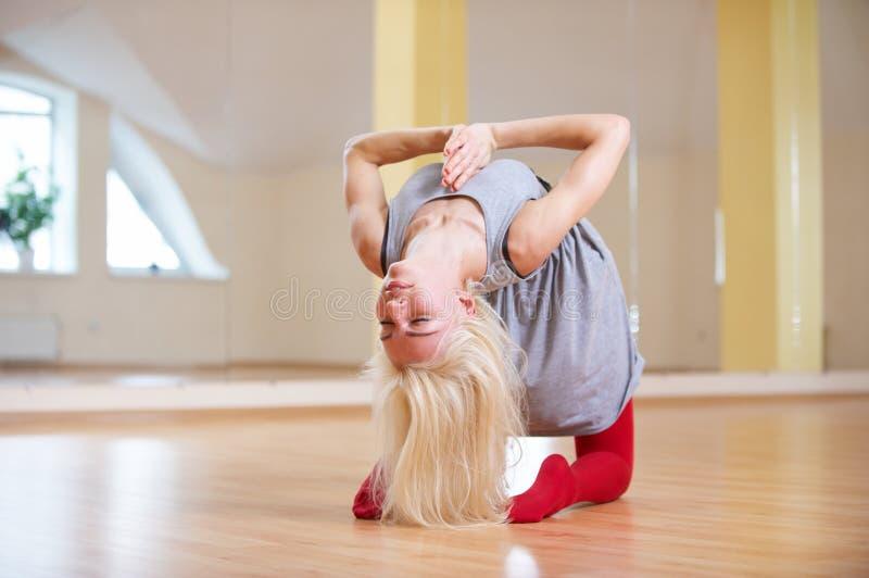 La mujer joven hermosa practica el asana Ushtrasana - actitud de la yoga del camello en la clase de la yoga imagen de archivo