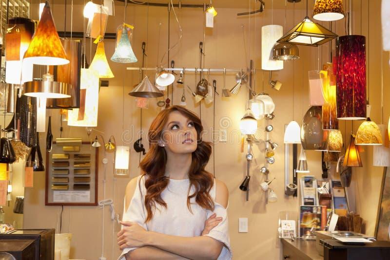 La mujer joven hermosa que hojeaba para las luces con los brazos cruzó en tienda fotos de archivo