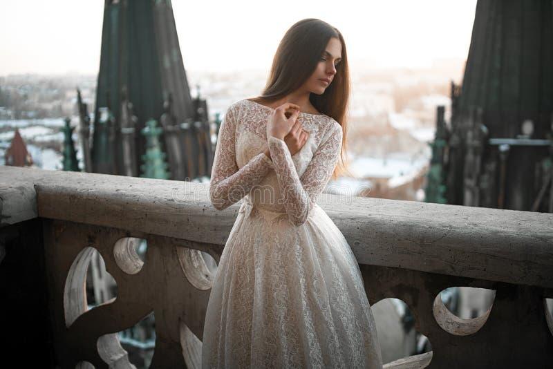 La mujer joven hermosa se coloca en el balcón contra la perspectiva de paisaje urbano fotos de archivo