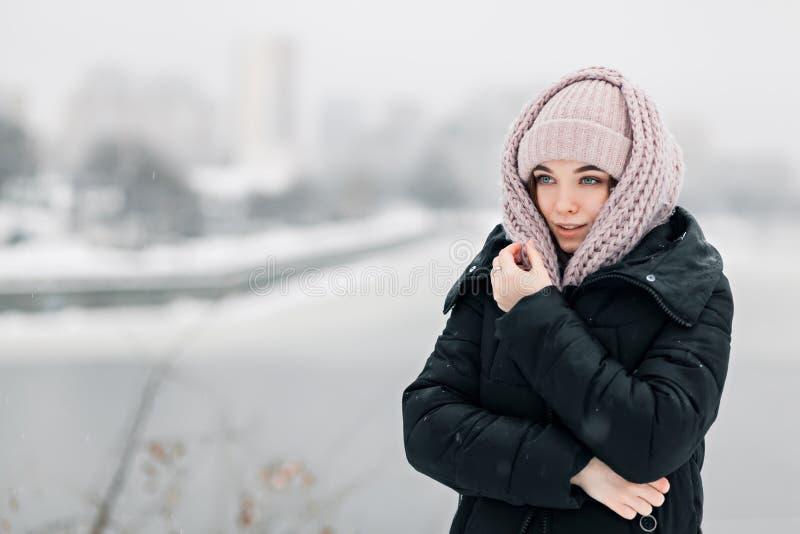 La mujer joven hermosa se coloca en el fondo de la ciudad nevosa en una bufanda y un sombrero fotos de archivo