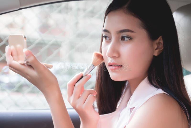 La mujer joven hermosa se sienta en coche en el asiento de conductor que mira el espejo que comprueba, cepillando compone imagenes de archivo