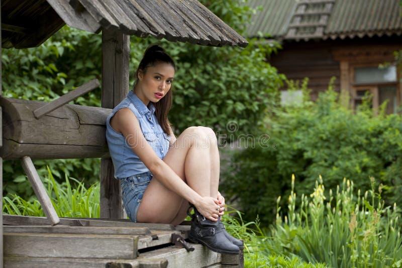 La mujer joven hermosa se sienta en un hoyo de madera en el parque imágenes de archivo libres de regalías