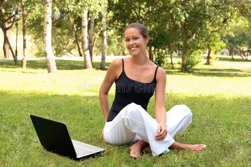 La mujer joven hermosa se sienta en una hierba en un parque imagen de archivo