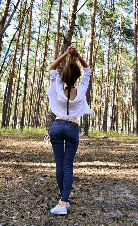 La mujer joven hermosa se sostiene el pelo en las manos fotos de archivo libres de regalías