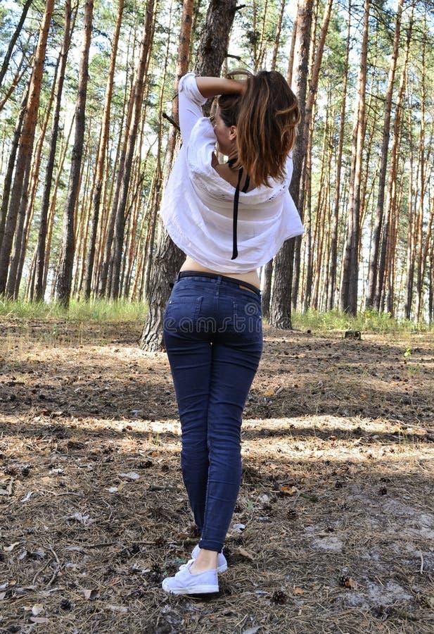 La mujer joven hermosa se sostiene el pelo en las manos imagen de archivo libre de regalías