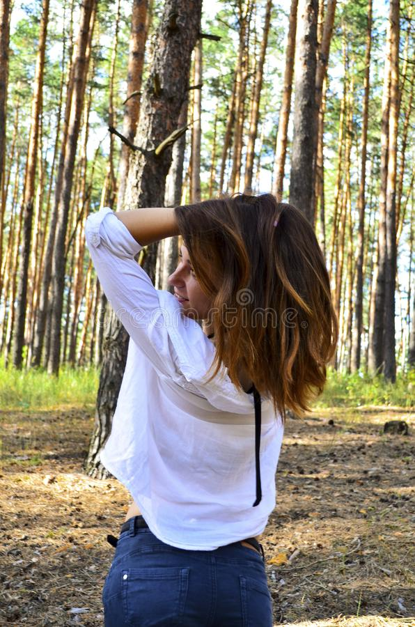La mujer joven hermosa se sostiene el pelo en las manos imagenes de archivo