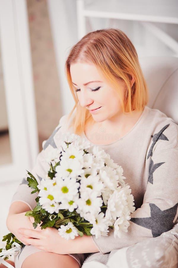 La mujer joven hermosa sienta la cabeza inclinada y sostiene un ramo de flores El retrato de una muchacha bonita en una luz hizo  fotografía de archivo