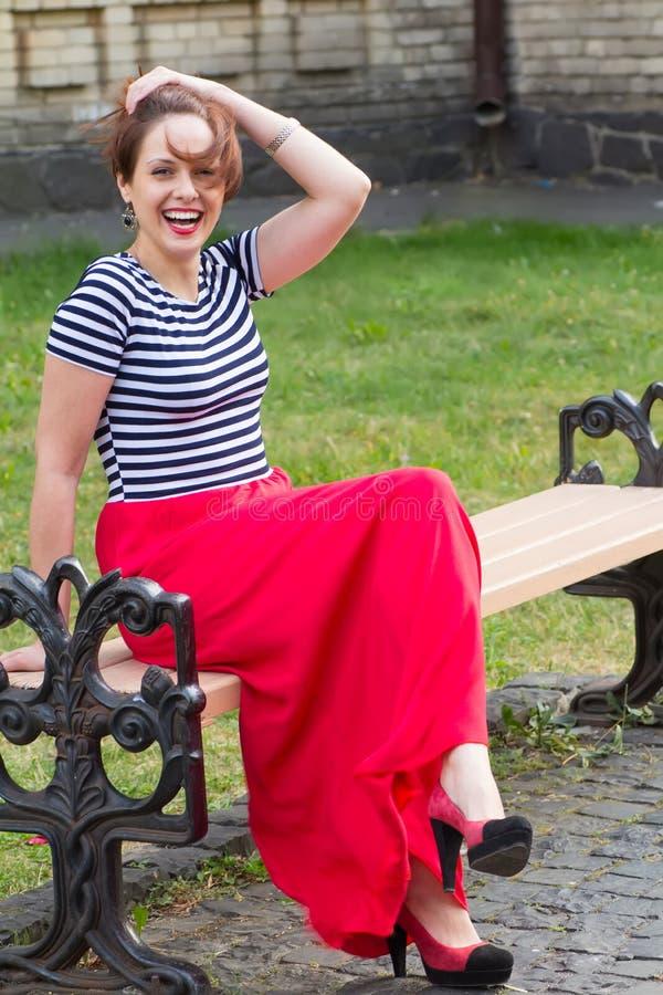 La mujer joven hermosa sonriente con cortocircuito oye en el chaleco y de largo la falda roja, sentándose en un banco al aire lib fotos de archivo