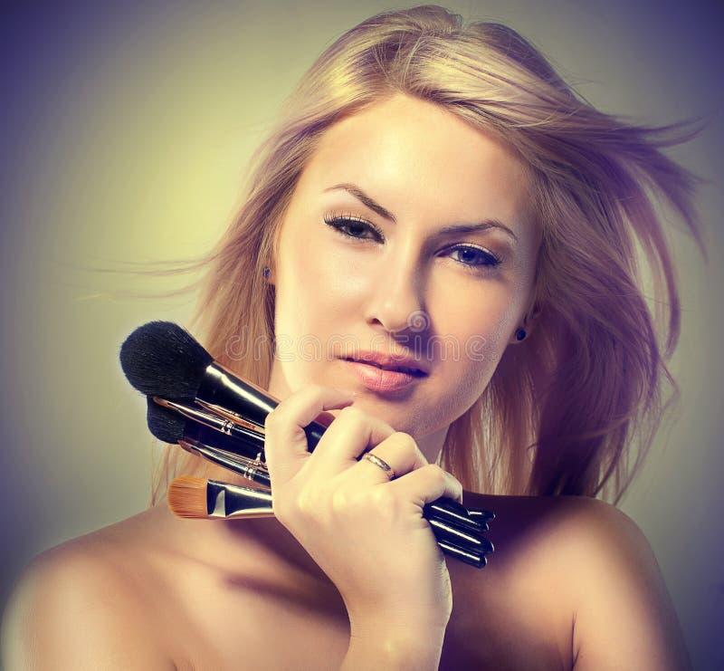 La mujer joven hermosa sostiene los cepillos del maquillaje fotografía de archivo