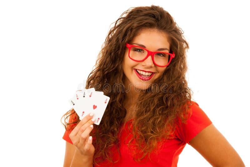 La mujer joven hermosa sostiene tarjetas del póker cuatro as aisladas encima fotografía de archivo