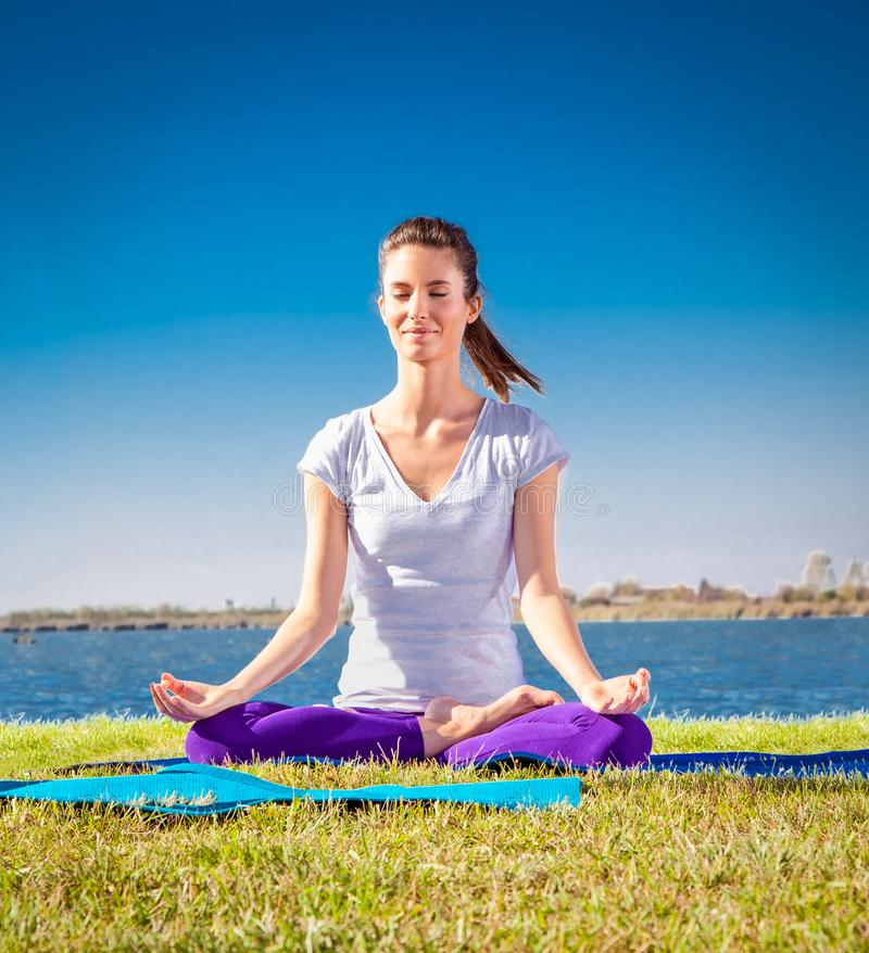 La mujer joven hermosa tiene una meditación en clase de la yoga imágenes de archivo libres de regalías