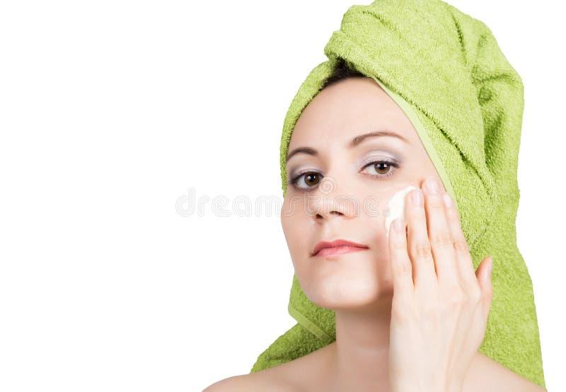 La mujer joven hermosa vestida en una toalla de baño hace la máscara cosmética en la cara industria de la belleza y cuidado de pi fotos de archivo libres de regalías
