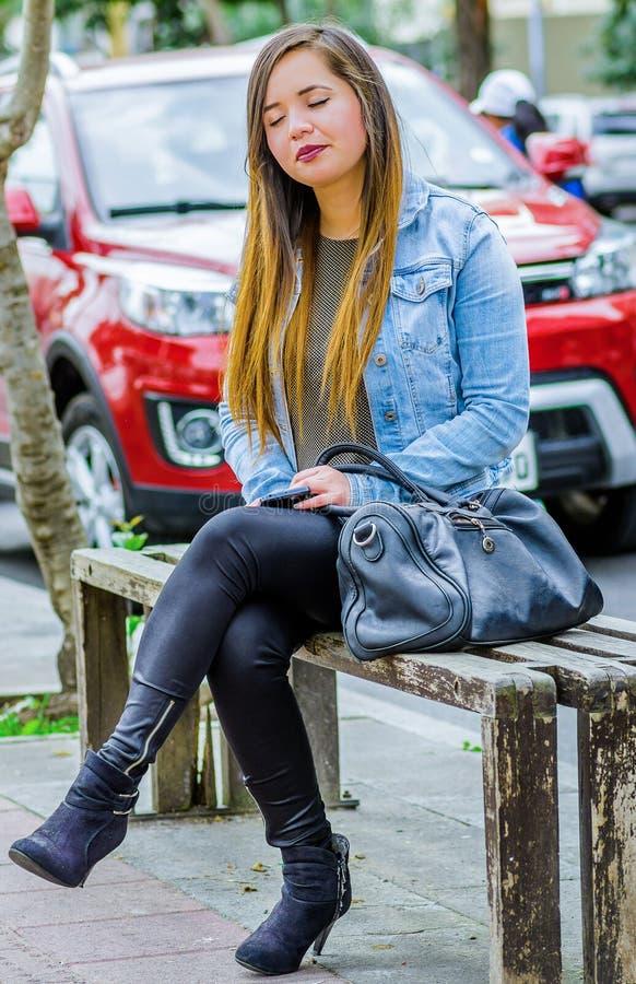 La mujer joven hermosa vistió bien sueño descendente en una silla pública en las calles de la ciudad de Quito, Ecuador foto de archivo libre de regalías