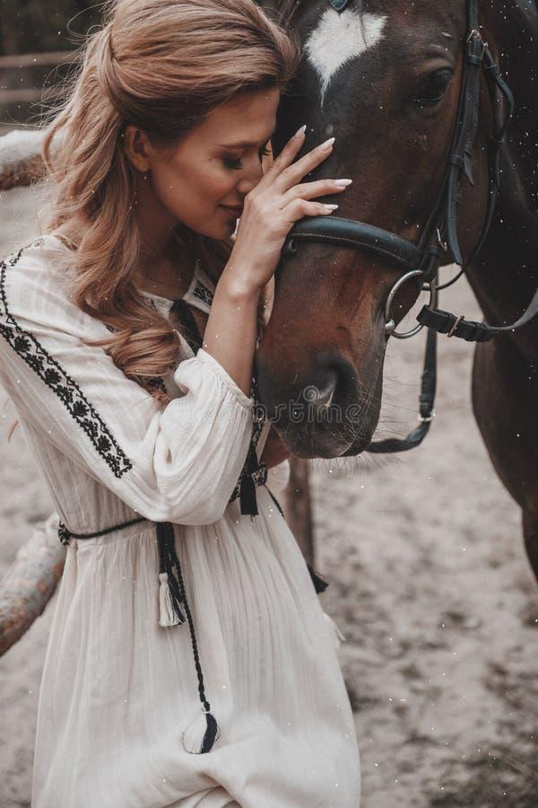 La mujer joven hermosa y delicada que lleva el vestido es de abarcamiento y que frota ligeramente del caballo en el rancho imagen de archivo libre de regalías