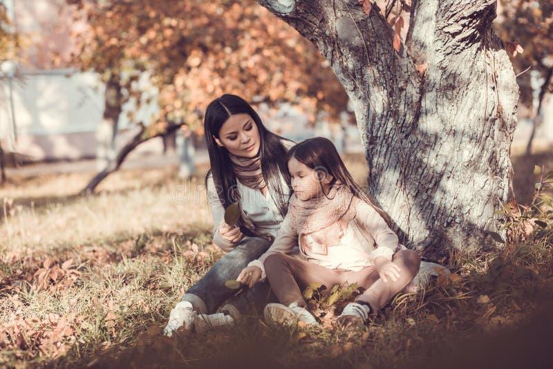 La mujer joven hermosa y su niño en otoño cultivan un huerto fotografía de archivo libre de regalías