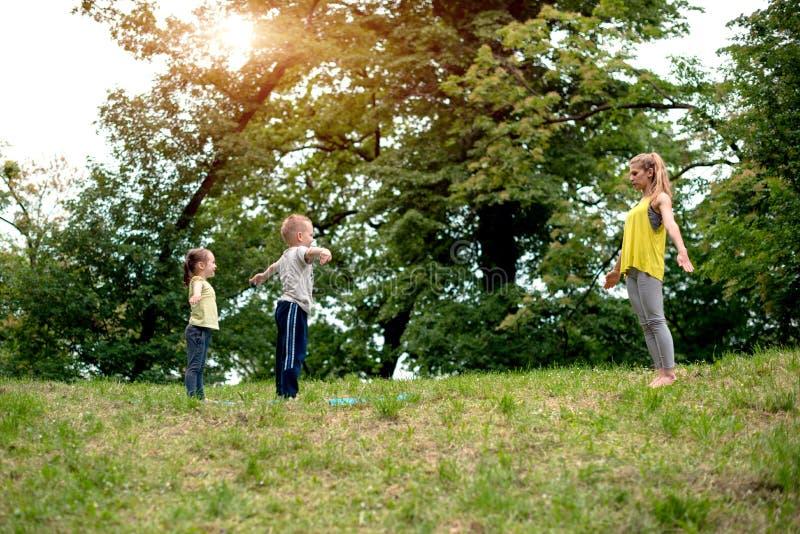 La mujer joven hermosa y sus niños encantadores son w sonriente fotos de archivo libres de regalías